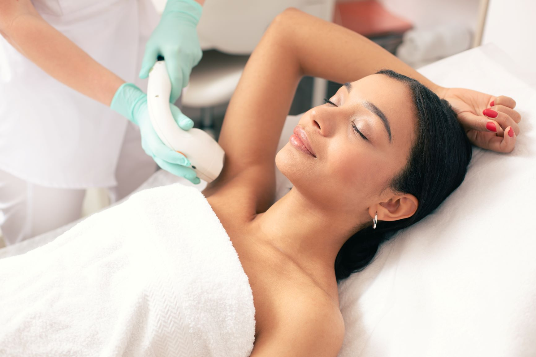 dark-haired woman receiving laser hair removal treatment